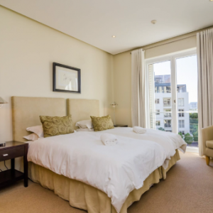 Twin beds with white bedding and patio view